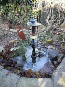 gefrorener Teich mit Gartenbrunnen